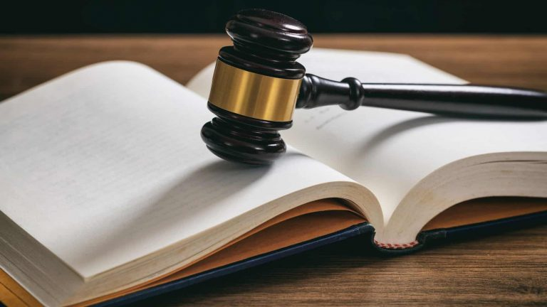 Law or auction gavel on an open book, wooden desk, dark background
